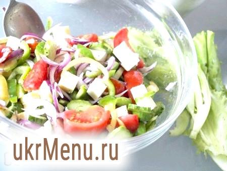 Фото - Бринзу (фету) нарізаємо кубиками. Рвемо руками листя салату і викладаємо на дно тарілки, туди ж відправляємо примушення помідори, цибулю, болгарський перець, огірки, посипаємо орегано, базиліком, перчимо, солимо. Бринзу додаємо в салат і перемішуємо всі інгредієнти з заправкою (трохи заправки залиште, вона знадобиться в кінці приготування страви). Якщо ви готуєте грецький салат з фетою, то цей ніжний сир краще додати після того, як змішаєте овочі з заправкою.