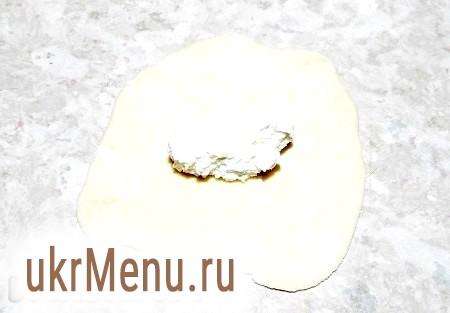Фото - Отриману порцію тіста (відрізаний невеликий шматочок тесту) розкачати в круг. На середину кола розмістити начинку із сиру.