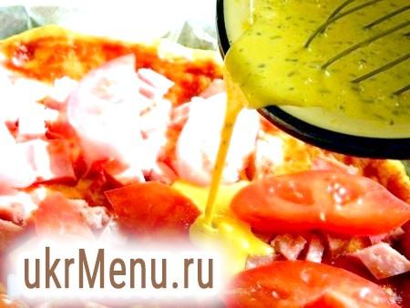 Фото - Викладаємо нарізану ковбасу і порізані помідори. Яйця змішуємо з майонезом, невеликою кількістю зелені, додаємо сіль, перемішуємо і заливаємо піцу по всьому об'єму.