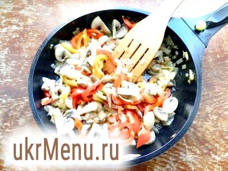 Фото - На рослинному маслі обсмажити цибулю, потім додати шампіньйони і перець і обсмажити всі разом.