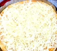Фото - Крок №2 - Посипати тісто великою кількістю натертого сиру,