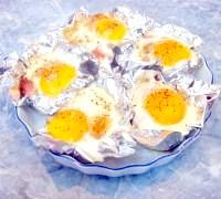 Фото - Крок №5 - Викласти у форму з фольги обжарку, зверху акуратно вилити яйце, намагаючись не пошкодити жовток. Посолити, поперчити. Формочки з яєчнею поставити в розігріту до 180 ° C духовку на 25-30 хвилин.