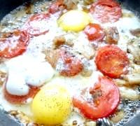 Фото - Крок №3 - на невеликому вогні обсмажити трохи помідори, перевернути і вбити яйця. Посолити за смаком. Смажити до готовності яєць, поки згорнеться білок. Зверху посипати чорним меленим перцем. Можна ще додати трохи часнику. Вимкнути газ.