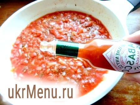 Фото - Очистити і обсмажити другу цибулину з рештою часником. Викласти до цибулі помідори з банки, додати сіль, перець, спеції і томатну пасту. Обережно додати гострий соус табаско.