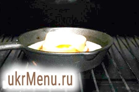 Фото - Всередину кільця з хліба розбити яйце, намагаючись зберегти жовток цілим. Посолити, не зачіпаючи жовтка, інакше на жовтку залишаться вмятинки від солі. Відправити нашу порційну сковорідку з яєчнею в хлібі в заздалегідь нагріту до 200 градусів духовку.